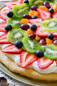 Fruit pizza on a soft sugar cookie crust and topped with creamy, thick cream cheese frosting. Recipe by sallysbakingaddiction.com