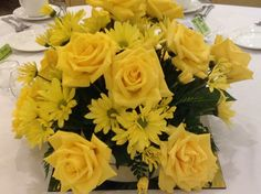 Centerpieces of yellow roses and daisies.