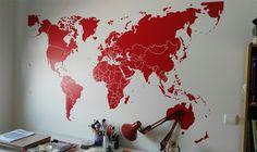 Vinilo decorativo Mapamundi con marcadores, en color rojo, de tamaño 210 x 120 cm, instalado en la pared de nuestro cliente.