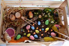 Voici notre bac sensoriel de Pâques. Une cagette, des billes d'argiles pour le fonds, de la mousse, un nid, des fleurs, lapin, poules... des œufs et encore des œufs! Des petits seaux pour le tri et des pinces pour attraper des œufs. Voila comment a terminé...