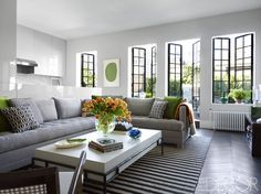 In the living room of designer Timothy Whealon's Manhattan apartment, the sofa, inspired by a Billy Baldwin design and covered in a linen by Christopher Farr Cloth, and the cocktail table are custom designs. An abaca rug by Merida tops chevron-patterned oak floors, and the steel doors and windows are by Crittall.