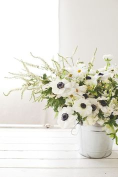 A galvanized bucket adds a farm fresh look to a glamorous bouquet / anemones