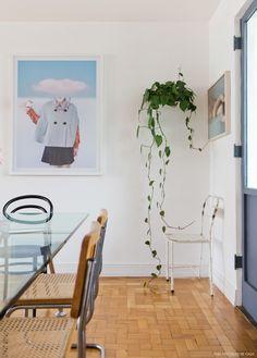 Sala de jantar com mesa de vidro, planta pendente e cadeira de ferro antiga.