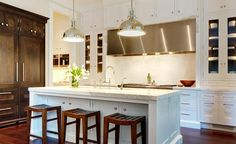 Gourmet kitchen features a row of cabinets placed above a long stainless steel hood situated over ...