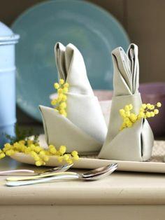 Zu Ostern darf die Tischdeko ruhig ein bisschen ausgefallener sein. Wie wäre es mit Servietten in Hasenform? Hier gibt es die Faltanleitung.