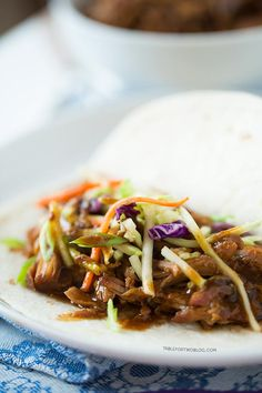 Slow cooker Korean tacos via tablefortwoblog.com. The tender & flavorful pork is wrapped inside a warm tortilla and topped with a tangy slaw!
