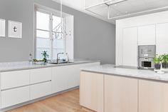 cuisine en blanc et gris clair aménagée avec un îlot fonctionnel doté d'un plan de travail en marbre blanc