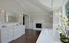Beautiful ensuite bathroom design with gray walls paint color, wainscoting, marble fireplace, wood floors in a chevron herringbone pattern, white bathroom vanity, rectangular pivot mirror, soaking tub, polished nickel sconces and orchid.