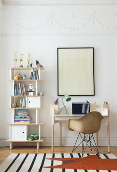 This adorable home office has a black adn white striped rug, open shelving unit made out of plywood with matching desk, molded chair, green desk light, framed artwork and wood flooring.