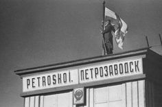 Finnish Army, WWII. Soldier of 1st Division raising Finnish flag on the roof of Petroskoi (Petrozavodsk) railway station.