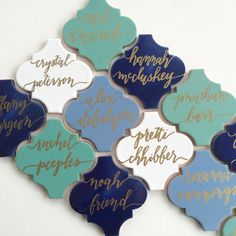 Gold calligraphy on blue and green tiles for escort card idea