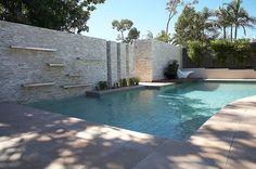white stone clad wall forms the perfect backdrop for this simple, yet elegant backyard. Stainless steel channels,