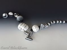 Asymmetric necklace of hollow beads.  Ikat, Mokume Gane and a patterned Tetra bead