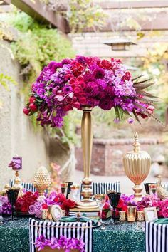 Jennifer Cole Flowers Pam Scott Photography - Elevated flower centerpiece on a gold stand with hot pink and magenta flowers