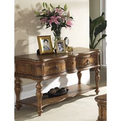 This striking table features a medium brown finish with light distressing. This furniture piece provides storage with one shelf and two drawers.
