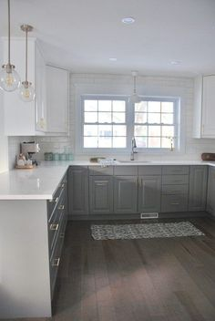A grey and white kitchen featuring a white subway tile backsplash, IKEA cabinets, hardwood floors, marble lookalike quartz countertop, and gold hardware.