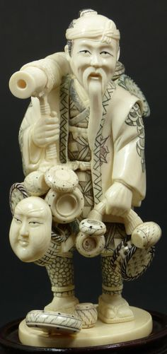 JAPANESE IVORY FIGURE OF TRAVELING MERCHANT SIGNED  Japanese hand carved ivory figure depicting a traveling merchant or craftsman carrying masks, baskets and bowls. He is wearing layered robe with etched polychromed patterns. Signed to bottom Jiang Chuan.