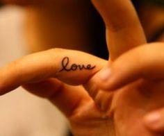 """Tatouage """"love"""" dans le creux du doigt."""