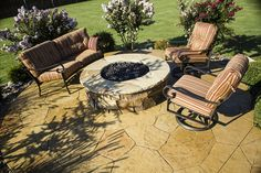 Stone fire pit with an elevated, stamped concrete patio surrounded with landscaping by Red Valley Landscape & Construction.