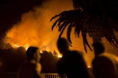 People watch as a forest fire burns out of control in Las Manchas, on the southwestern part of La Palma island