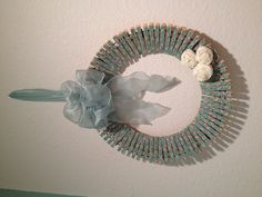 Clothespin wreath for my laundry room! Here's how I made it: mod podged ribbon onto regular size clothes pins and clipped the pins onto wreath wire. Rolled up the roses out of fabric and made a bow and hanger out of ribbon and that's it! :)