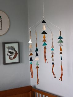 I love this woman's sweet mobiles using leather and feathers.  She'll have a booth in the same craft fair as me in August!  Also loving that handsome little raccoon in the background.