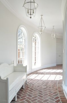 The diagonal lines in the brick flooring give a sense of movement as if you were already headed down the hallway. The rough texture of the brick flooring adds warmth to this neutral room by bringing a little bit of the outside in. The curve of the hallway is accent by the curve in the windows that are allowing the natural light in to warm up the white walls. The