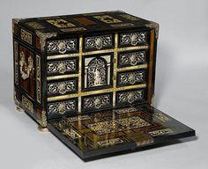 Ориентировочная цена: CHF4,000 - CHF6,000 Описание: ИНТАРСИЯ шкафа,Италия, 17 век. Эбенового дерева, розового дерева и слоновой кости, с гравировкой и инкрустацией . Интерьер с 10 ящиками, сгруппированными вокруг центральной двери, открывая отсек и 2 малыми ящиками. Посеребренные бронзовые и латунные крепления. 50x32x39 см. 2 ключа.