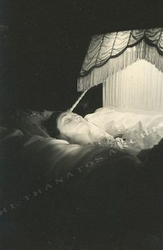 postmortem photo of a woman resting in an illuminated coffin. An artistic and unusual shot dating from about 1920.