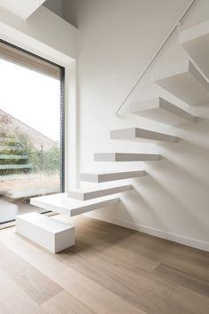 Let the magic in! Een zwevende trap in witte Corian® uitvoering trekt de aandacht en geeft tegelijk een ingetogen indruk door zijn minimalistisch design. De bijpassende strakke leuning verhoogt niet alleen het comfort maar creëert ook extra sfeer door de indirecte ledverlichting.