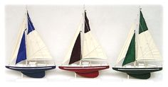 Each is made from handpainted wood with canvas sails. The sailboats are attached to their white display stands and do not come apart.