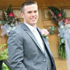 Groom: wedding: Gray tux, silver tie, pink flower