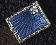 A JEWELED SILVER-GILT AND GUILLOCHÉ ENAMEL BROOCH   MARKED FABERGÉ, WITH THE WORKMASTER'S MARK OF MICHAEL PERCHIN, ST. PETERSBURG, INDISTINCT DATE MARK, CIRCA 1900  Rectangular, the body enameled in translucent blue over a sunburst guilloché ground, emanating from an inset rose-cut diamond in the upper right corner, all within a rose-cut diamond border, the reverse with mounted pin, with later safety chain, marked on reverse