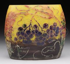 "DAUM NANCY FRENCH CAMEO VASE. Pillow shaped vase depicts an art nouveau design of purple grapes with multicolored foliage and stems set on a vibrant yellow to purple mottled ground. Signed ""Daum Nancy"" with Cross of Lorraine in cameo to side of vase."