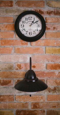 Brick wall interior with clock and lamp