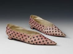 This style of heeled shoe, made of pastel coloured kid leather with painted or stencilled patterns, with an exaggerated pointed toe, was popular in the latter years of the 18th century. It was much simpler than previous women's styles which had tended to be made of leather and have a pronounced heel. In 1801, the Lady's Magazine featured illustrations of similar spotted kid shoes. The Victoria and Albert Museum collection