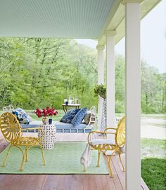 The iron daybed on the front porch of this New York farmhouse makes the space comfortable and the family's preferred hangout.   - CountryLiving.com
