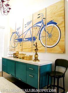 """vintagerevivals.blogspot.com: The hands down greatest thing in here is the tandem bicycle art by Jonathan from Olson Ink. All I did was tell him that I wanted a tandem old school bike in cobalt and white. He painted it on a 8'x4'x1"""" plywood with a wood veneer.  The wood was stained a light Honey Blonde color before he started painting.  Then when he was all done he cut it into 5 sections."""