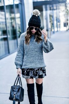 Flaunt and Center Houston style and fashion blogger Tiffany Jais wearing a chunky knit grey sweater by revolve and a printed skirt by revolve clothing, with a black pom pom beanie, and over the knee boots | Streetstyle