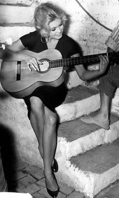 Brigitte Bardot playing guitar.