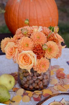 vase en verre rempli de fleurs d'automne orange, glands et noisettes