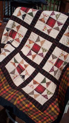 EVENING STAR - Red plaid centers brighten up abundant plaids in each evening star block.