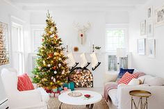 Jennaea put Christmas magic in overdrive in the family room, where a cardboard deer watches over the jolly scene. Taking a cue from the throw pillows, the family twirled up the tree with papier-mâché ornaments in red and blue, a fresh twist on traditional red and green. For a frosty finish, she hung ice-skate stockings; their nubby white felt complements other neutral textures in the room such as the slip-covered sofa.