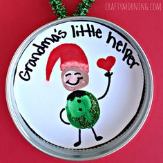 """Have your kids make a fingerprint elf ornament out of a mason jar lid! It's a cheap and meaningful gift at Christmas. Write """"Grandma's Little Helper"""" on the inside."""