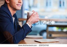Coffee time. Side view cropped image of handsome young man enjoying coffee in cafe while sitting at the table with digital tablet laying near him