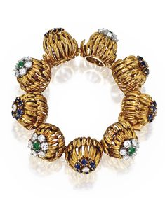 18 KARAT GOLD, DIAMOND AND COLORED STONE BRACELET, FRANCE Composed of textured gold flowerheads of openwork design, set with round diamonds weighing approximately 4.35 carats, further accented by 30 round sapphires and four round emeralds, gross weight approximately 51 dwts, length 5¾ inches, signed Made in Paris, France, with French obus mark. Estimate 8,000 — 12,000 USD  LOT SOLD. 12,500 USD