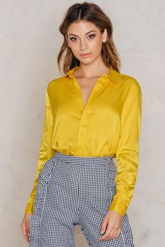 Go for an out of this world look with this amazing shirt. The Satin Shirt by NA-KD Trend comes in yellow and features a satiny material, a collared neck, three button closures at each cuff and buttons down the front. Complete this look with jeans and mule heels!