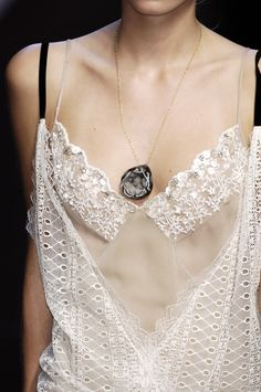 I would wear this with a more delicate necklace, possibly just a very thin gold chain and a small charm. The pendant really draws away from the delicate fabric.