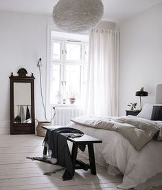 Dark wood accents in a white bedroom