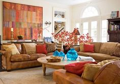 Rusted Palette with Pops of Blue...This family room's earthy palette of rusted browns, reds, and burnt orange is punctuated by a trio of vibrant aqua glass vases. The worn leather of the sectional sofas add a note of welcoming comfort.  Traditional Home